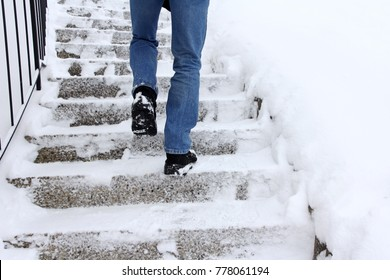 Risk of slipping when climbing stairs in winter. A man goes up a snow-covered staircase