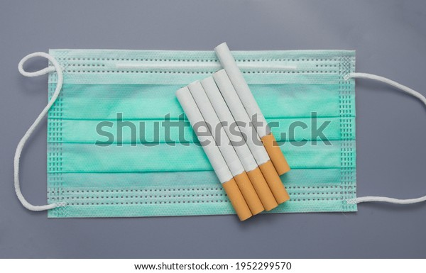 Risk of smokers with covid. Cigarettes are on the background of a medical mask