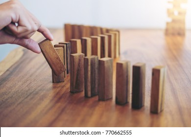 Risk and strategy in business, Close up of businessman hand gambling placing wooden block on a line of domino.