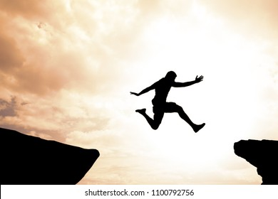 Risk and success concept of brave confident man jumping over mountain gap