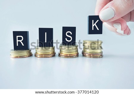 Risk text stacked upward on coins with cool image temperature as High Risk Business Concept