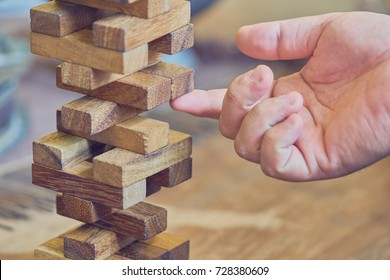 The risk will happen.Hand of engineer playing a blocks wood game on wood table vintage tone. architectural project .as background business concept with copy space.