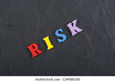 RISK word on black board background composed from colorful abc alphabet block wooden letters, copy space for ad text. Learning english concept