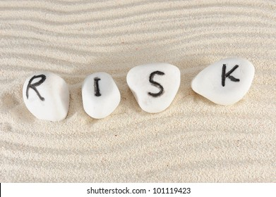 Risk word on group of stones with sand as background