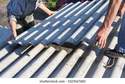 Risks of Asbestos Roofs, Asbestos Roof Removal. Asbestos removal roof works. House with old, danger asbestos roof tiles repair.