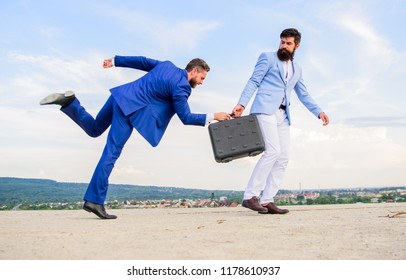 Risky transaction. Businessman takes away briefcase from business partner. Fraud and extortion concept. Men suits handover briefcase. Rascal racketeer extortionist cheating business transaction.