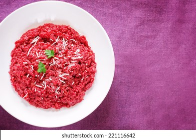 risotto with beetroom on a purple wood background. tinting. selective focus on parsley