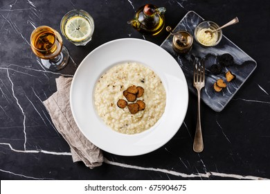 Risotto with black truffle on plate on dark marble table background