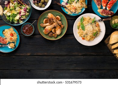 Risotto with cherry tomatoes, basil and parmesan cheese, roasted chicken legs and snacks on a dark wooden table with copy space. Italian food table, top view