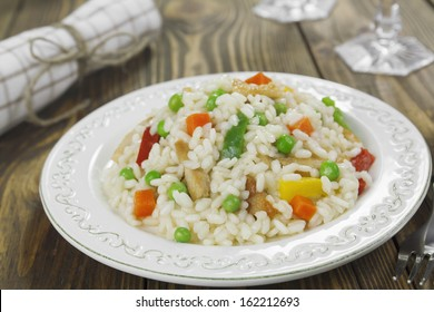 Risotto with chicken and vegetables in the plate on a wooden table