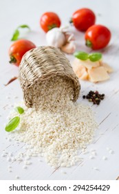 Risotto ingredients - rice, cheese, garlic, basil, oil, tomatoes, white wood background