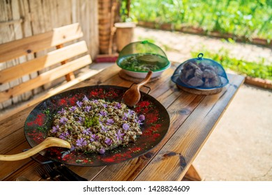 Risotto with mushrooms and flowers on wooden table