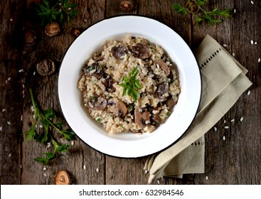 Risotto with mushrooms on an old wooden background. Rustic style.