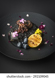 risotto with octopus and blueberries on a black plate on a black background