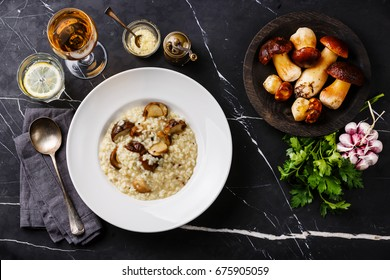 Risotto with porcini mushroom on plate and raw mushrooms on dark marble table background
