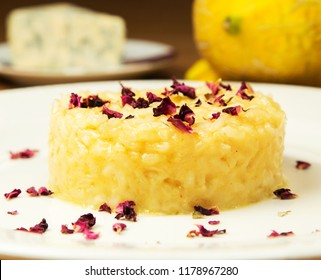 Risotto with pumpkin and parmesan cheese decorated with dry rose in restaurant table setting