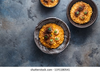 Risotto with pumpkin and scallops, on stone background, copy space