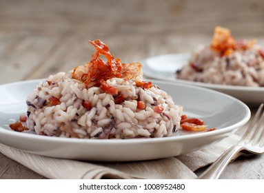 Risotto with  red radicchio and crispy bacon (speck) close up