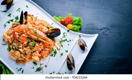 Risotto with seafood and royal shrimp. On a wooden background. Top view. Free space for text.