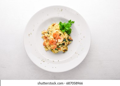 Risotto with shrimp. On a wooden background. Top view. Free space for your text.