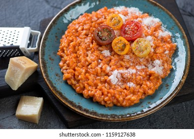 Risotto with tomatoes topped with grated parmesan and fresh sliced cherry tomatoes, studio shot
