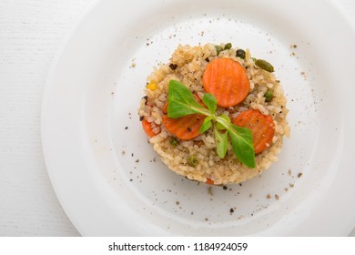 Risotto with vegetables and cappers on a white plate