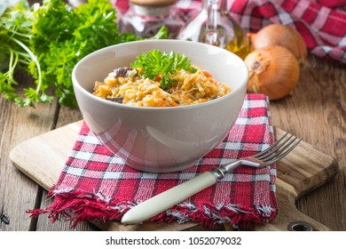 Risotto with vegetables on a wooden table.
