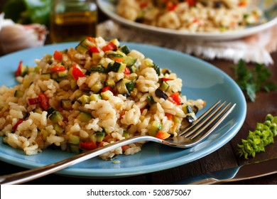 Risotto with vegetables on a wooden table close up