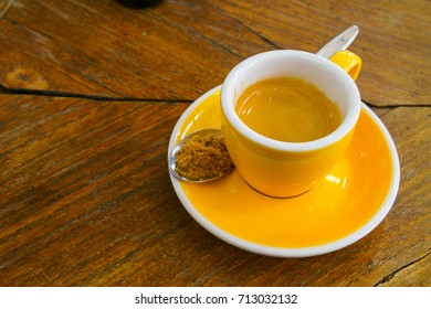 ristretto or espresso coffee shot in yellow cup with  spoon of brown sugar on old wooden table. copy space for text.