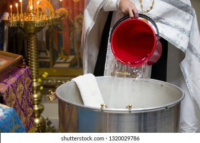 The rite of baptism. Priest prepare to baptize the child. Font for taking faith.Priest pours water into the bath for baptism