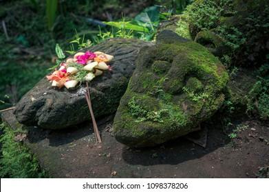 Ritual handmade gift on the stone altar in Goa Gajah, Bali, Indonesia