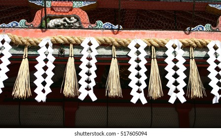 Ritual Japanese shimenawa rope from rice straw - shimenawa and Shide - zigzag paper tape on the gate of the temple. The symbols of religion - Shinto. Kyoto. Japan.