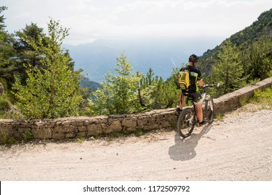 Riva del Garda, Brescia, Italy - August 16, 2018: cyclist on an ancient dirt road in the woods above lake Garda. The area is renowned for mountain biking trails.