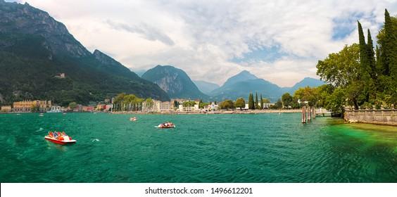 Riva del garda, Italy - 07 20 2017: Coast of emerald lake Lago di Garda near the city Riva del Garda, mountains (alps) and cloudy sky in the background