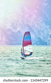 Riva del Garda, Italy - 21 June 2018: Windsurfer Surfing The Wind On Waves In Garda Lake, Recreational Water Sports, Extreme Sport Action. Recreational Sporting Activity. Summer Fun Adventure