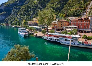 Riva del Garda,Lago di Garda ,Italy - 9 September 2019:View to the port of Riva del Garda and the beautiful Riva del Garda town with the square 4 November, Garda lake in the summer time