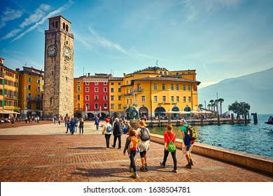 Riva del Garda,Lago di Garda ,Italy - 13 October 2019:Tourists enjoying a walk around Lake Garda, colorful autumn in Riva del Garda surrounded by mountains, Trentino Alto Adige region,