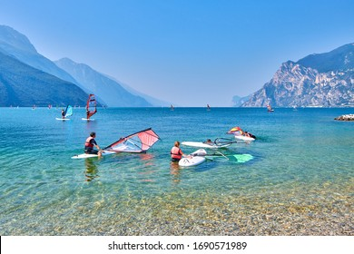 Riva del Garda,Lago di Garda ,Italy  - 26 June 2019: Windsurfer surfing the wind on waves In Garda Lake, riders surfing at high speed on Lake Garda, Recreational Water Sports, Extreme Sport Action