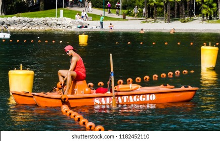 Riva, Lake Garda, Italy - September 6, 2018: Lifeguard on a small twin hulled rescue (Salvataggio) boat checking flotation buoys, near lake's edge. People in background. Trentino.