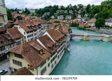 River Aare winding through the downtown Bern, the capital of Switzerland, lined by trees and cottages with a foot bridge going across.