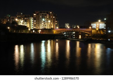 the river aire in leeds at night showing buildings on both sides of crown point bridge and the weir