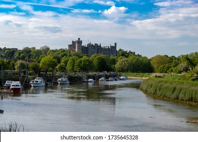 River Arun with boats moored on the riverbank overlooked by Arundel Castle in the background.
