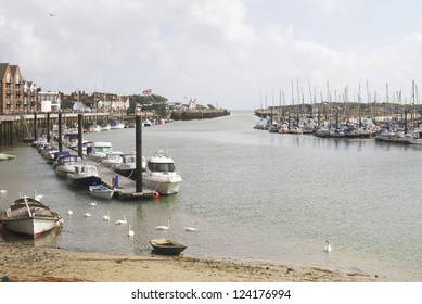 River Arun at Littlehampton. West Sussex. England. With moored boats and apartments along riverside promenade.