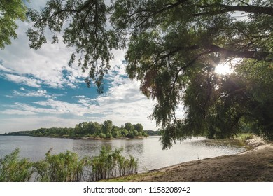 The river bank, the blue sky with clouds on the background