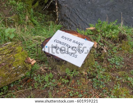 River Bank Conservation in Progress Sign Attached to a Tree Stump next to the Little Dart River in the Village of East Worlington in Rural Devon, England, UK