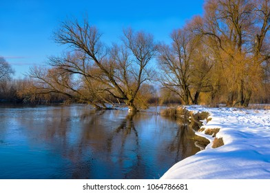 River bank is covered with snow but river without ice