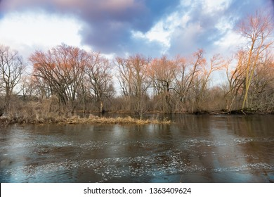River banks in early spring.  Clouds reflecting in moving water of stream.