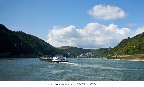 A river barge called the Velocity maneuvers past some shallow water with dangerous rock outcrops in a section of the middle Rhine River in Germany, St. Goar. Aug 2019