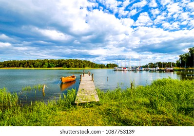 River boat at wooden river pier in summer cloudy landscape. Summer river with yacht club. Wooden piet at summer river