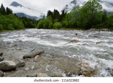 The river of Campo Tures flows between the rocks and the green trees. In the background, the mountains surrounded by the clouds.